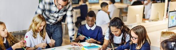 Teacher helps student solve math problem